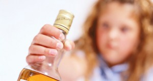 blurred view of a young girl (6-8) holding a bottle of scotch whisky